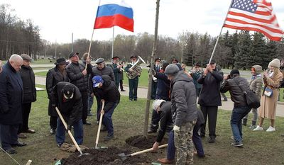 """Russians and Americans plant """"Friendship"""" tree in the """"Victory Park"""" on Poklonnaya Gora in Moscow on April 25, 2021."""