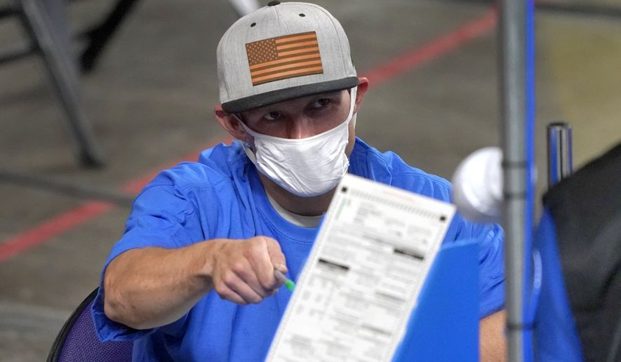 Maricopa County ballots cast in the 2020 general election are examined and recounted by contractors working for Florida-based company, Cyber Ninjas, Thursday, May 6, 2021 at Veterans Memorial Coliseum in Phoenix. The audit, ordered by the Arizona Senate, has the U.S. Department of Justice saying it is concerned about ballot security and potential voter intimidation arising from the unprecedented private recount of the 2020 presidential election results. (AP Photo/Matt York, Pool) **FILE**