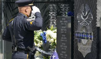 In this file photo, Miami Beach Police Sgt. Enrique Rios salutes a memorial during a ceremony to honor fallen police officers, Thursday, May 6, 2021, at the Miami Beach Police Headquarters in Miami Beach, Fla. (AP Photo/Wilfredo Lee)  **FILE**