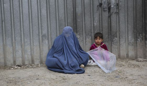 In this May 2, 2020 file photo, a woman waits to receive alms with her daughter during the Muslim fasting month of Ramadan, in Kabul, Afghanistan. (AP Photo/Rahmat Gul, File)  **FILE**