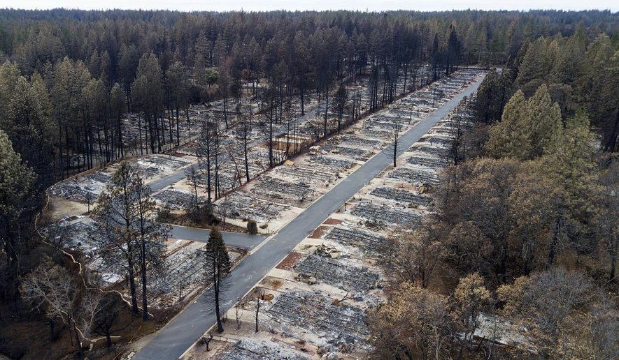 FILE - In this Dec. 3, 2018, file photo, charred footprints of homes leveled by the Camp Fire line the streets at the Ridgewood Mobile Home Park retirement community in Paradise, Calif. A trust approved by a federal judge to help compensate victims of deadly California wildires sparked by Pacific Gas & Electric equipment paid survivors just $7 million while racking up $51 million in overhead in its first year of operation, KQED News reported. (AP Photo/Noah Berger, File)