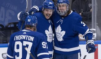 Toronto Maple Leafs center Auston Matthews (34) celebrates his 40th goal of the season with teammates Joe Thornton (97) and Justin Holl (3), during the third period of an NHL hockey game against the Montreal Canadiens on Thursday, May, 6, 2021, in Toronto. (Frank Gunn/The Canadian Press via AP)