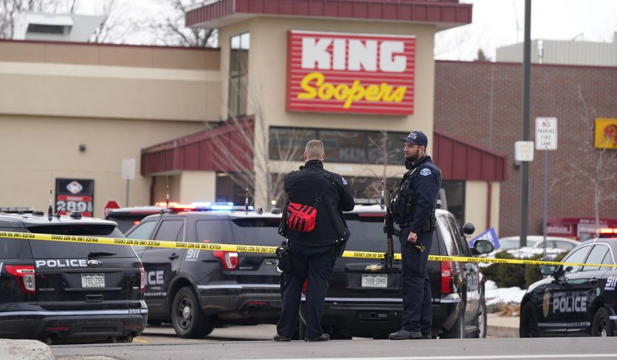 FILE - In this March 22, 2021, file photo, police work on the scene outside of a King Soopers grocery store where a shooting took place in Boulder, Colo. A man charged with killing 10 people at the supermarket surrendered after being shot by a police officer who waited for him to come into view down a store aisle, according new information about the shooting released Thursday, May 6, 2021. The details were contained in a district attorney's report that found Boulder officer Richard Steidell was justified in shooting Ahmad Alissa and said his shots stopped the attack. (AP Photo/David Zalubowski, File)