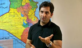 Raslan Haddad, the presenter of the local TV prank show, Tannab Raslan, stands in front of a map of Iraq during an interview with The Associated Press in Baghdad, Iraq, Tuesday, May. 5, 2021. Responding to viewer outrage, Iraq's media regulator canceled the  show that lured guests into simulated ambushes by militants, forcing participants and viewers to relive the fear that was widespread under the rule of the Islamic State group. (AP Photo/Hadi Mizban)