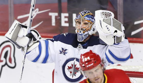 Winnipeg Jets goalie Connor Hellebuyc celebrates the team's 4-0 win as Calgary Flames' Brett Ritchie skates past, at the end of an NHL hockey game Wednesday, May 5, 2021, in Calgary, Alberta. (Larry MacDougal/The Canadian Press via AP)