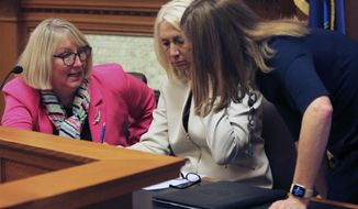 Kansas state Sens. Molly Baumgardner, left, R-Louisburg; Renee Erickson, center, R-Wichita, and Dinah Sykes, D-Lenexa, huddle during talks with the House over the final version of school funding and education policy legislation, Thursday, May 6, 2021, at the Statehouse in Topeka, Kan. Their talks are under way even though Republican legislative leaders and Democratic Gov. Laura Kelly have not struck a deal on education issues. (AP Photo/John Hanna)