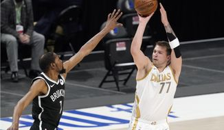 Brooklyn Nets forward Kevin Durant, left, defends as Dallas Mavericks guard Luka Doncic (77) shoots in the first half of an NBA basketball game in Dallas, Thursday, May 6, 2021. (AP Photo/Tony Gutierrez)