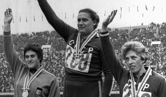 FILE - In this Oct. 20, 1964 file photo, Tamara Press, center, raises her hand on victory stand after winning the women's shot put finals with a new Olympic record of 18.14 meters. Three-time Olympic champion Tamara Press has died at the age of 83. The Russian track federation says Press died in the hospital on April 26, 2021 without giving a cause of death. Press competed for the Soviet Union and won gold in the shot put and silver in the discus at the 1960 Rome Olympics. She won gold in both events four years later at the 1964 Tokyo Games. (AP photo, file)