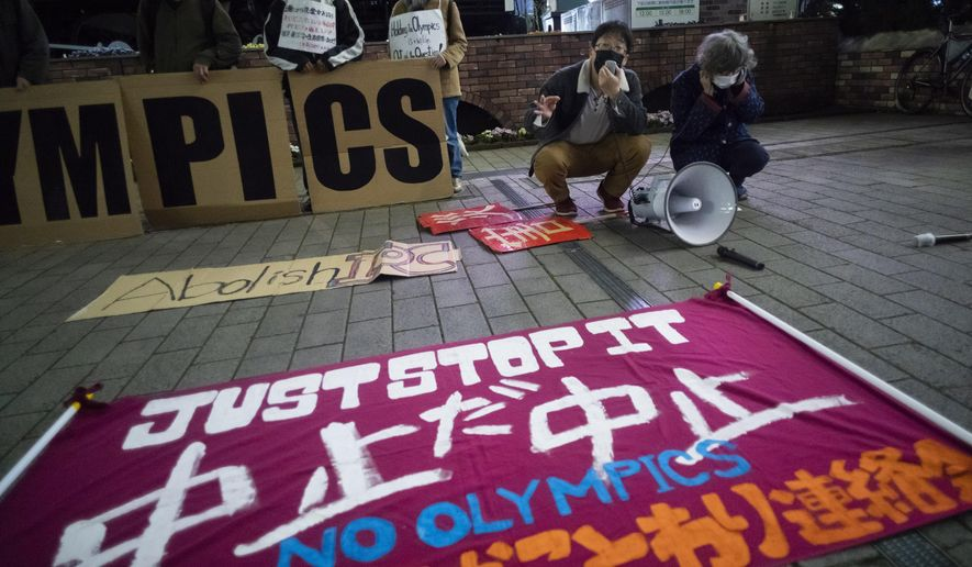 """In this March 25, 2021, file photo, a """"No Olympics"""" banner is placed by protesters in Tokyo during a demonstration against the going ahead of the Tokyo 2020 Olympic and Paralympic Games. (AP Photo/Hiro Komae, File)"""
