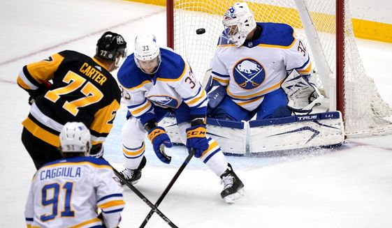 Pittsburgh Penguins center Jeff Carter (77) pust a shot past Buffalo Sabres goaltender Michael Houser (32) with Sabres' Colin Miller (33) defending during the first period of an NHL hockey game in Pittsburgh, Thursday, May 6, 2021. It was Carter's second goal of the first period. (AP Photo/Gene J. Puskar)