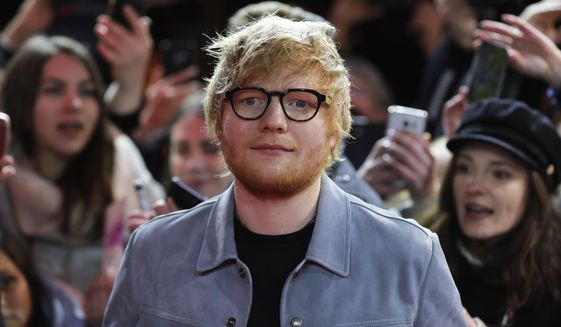 """FILE - In this Friday, Feb. 23, 2018 file photo, singer-songwriter Ed Sheeran arrives for the screening of the film 'Songwriter' during the 68th edition of the International Film Festival Berlin, Berlinale, in Berlin, Germany. Sheeran is the new shirt sponsor for third-division English soccer club Ipswich, it was announced Thursday, May 6, 2021. The """"Shape of You"""" singer signed a one-year deal to sponsor the men's and women's shirts next season. The 30-year-old musician grew up in the area and is a longtime Ipswich fan.(AP Photo/Markus Schreiber, file)"""