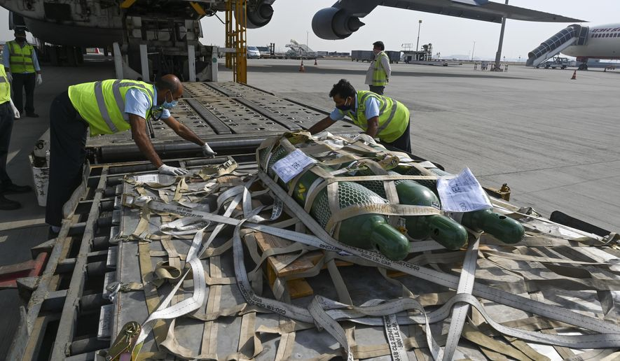 FILE - In this April 30, 2021, file photo, relief supplies from the United States in the wake of India's COVID-19 situation arrive at the Indira Gandhi International Airport cargo terminal in New Delhi, India. India's large diaspora is tapping its wealth, growing political clout and expertise to help India combat a catastrophic coronavirus surge that has led to desperate pleas for oxygen and left people to die outside overwhelmed hospitals. (Prakash Singh/Pool via AP, File)