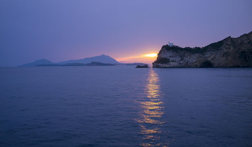 FILE - In this Oct. 1, 2016 file photo, sunset is over the Italian Islands of Procida and Ischia in the Bay of Naples, Italy. Italy on Friday will open a mass vaccination campaign on small, remote islands where numbers of residents and health care services are limited. The office of Italy's virus czar said the campaign would initially target the Aeolian Islands north of Sicily and Isola Capraia off the Tuscan coast. Other remote areas on the mainland _ isolated villages in the Alps and Apennine mountains _ might be targeted with similar campaigns. (AP Photo/Alexander Zemlianichenko)