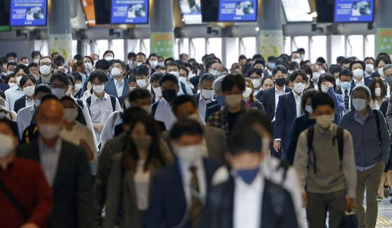 Commuters wearing face masks walk through a station passageway in Tokyo Friday, May 7, 2021. Japan is set to expand and extend a state of emergency in Tokyo and other areas through May 31 as the coronavirus continues spreading and uncertainty grows about safely holding the Olympics just 11 weeks away. (Yuta Omori/Kyodo News via AP)
