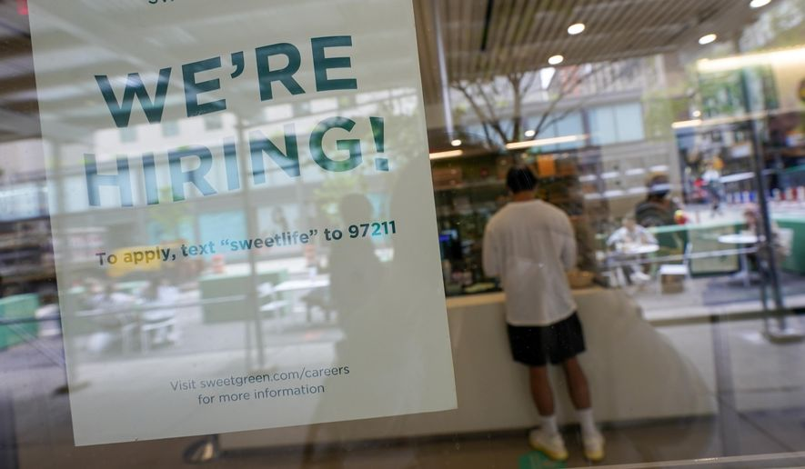 A sign announcing they are hiring hangs in the window of a restaurant in the Greenwich Village neighborhood of Manhattan in New York, Tuesday, May 4, 2021. Some restaurants in New York City are starting to hire employees now that they can increase their indoor dining to 75% of capacity starting May 7. (AP Photo/Mary Altaffer)