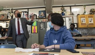 Secretary of Education Miguel Cardona, left, talks to 12th grade art student Oscar Quezada at White Plains High School, Thursday, April 22, 2021, in White Plains, N.Y. Cardona visited as part of the 'Help is Here' tour. The school reopened to all students on April 12. (AP Photo/Mark Lennihan)