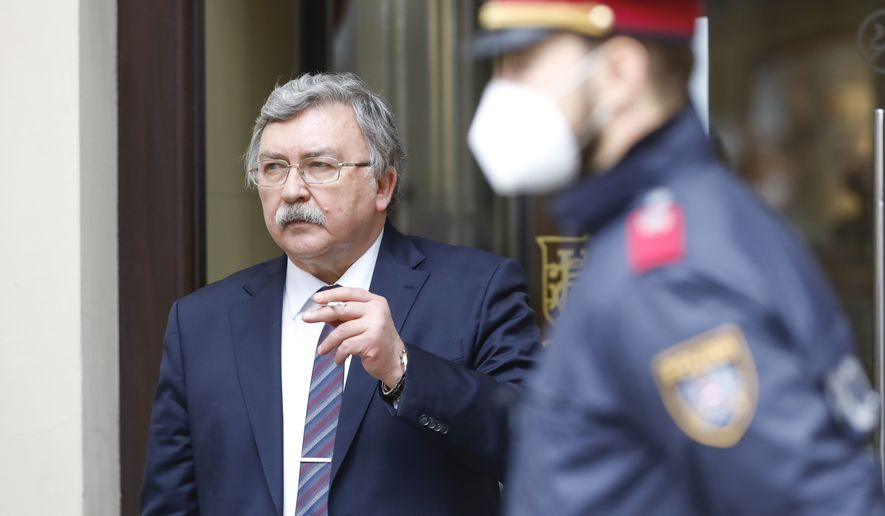 """Russia's Governor to the International Atomic Energy Agency (IAEA), Mikhail Ulyanov, has a cigarette break outside of the """"Grand Hotel Wien"""" where closed-door nuclear talks with Iran take place in Vienna, Austria, Friday, May 7, 2021. (AP Photo/Lisa Leutner)"""