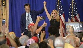 Rep. Matt Gaetz, R-Fla., left, and Rep. Marjorie Taylor Greene, R-Ga., raise their arms after addressing attendees of a rally, Friday, May 7, 2021, in The Villages, Fla. (AP Photo/Phelan M. Ebenhack)