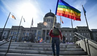 FILE - In this March 15, 2021, file photo demonstrators gather on the steps of the Montana State Capitol protesting anti-LGBTQ+ legislation in Helena, Mont. Gov. Greg Gianforte signed a bill Friday, May 7, 2021, banning transgender athletes from participating in school and university sports according to the gender with which they identify, making Montana the latest of several Republican-controlled states to approve such measures this year. (Thom Bridge/Independent Record via AP, File)
