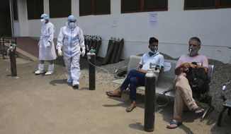 COVID-19 patients receive oxygen outside a government run hospital in Jammu, India, Friday, May 7, 2021. With coronavirus cases surging to record levels, Indian Prime Minister Narendra Modi is facing growing pressure to impose a harsh nationwide lockdown amid a debate whether restrictions imposed by individual states are enough. (AP Photo/Channi Anand)