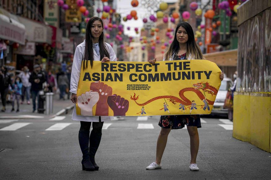 Dr. Michelle Lee, left, a radiology resident, and Ida Chen, right, a physician assistant student, unfold a banner Lee created to display at rallies protesting anti-Asian hate, Saturday April 24, 2021, in New York's Chinatown.  (AP Photo/Bebeto Matthews)