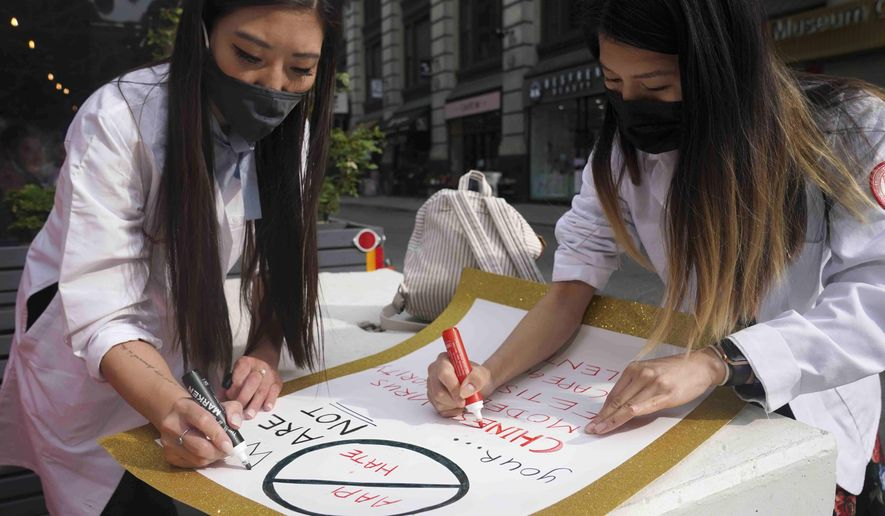 Dr. Michelle Lee, left, a radiology resident, and Ida Chen, right, a physician assistant student, prepare posters they carry at rallies protesting anti-Asian hate, Saturday April 24, 2021, in New York's Chinatown. Lee, who is Korean-born, and Chen, who is American-born Chinese, join medical professionals of Asian and Pacific Island descent who feel the anguish of being racially targeted because of the virus while toiling to keep people from dying of it. (AP Photo/Bebeto Matthews)