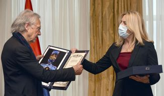 Austrian author Peter Handke, left, receives the Order of the Republika Srpska from President of Republika Srpska Zeljka Cvijanovic during the ceremony in Banja Luka, Bosnia, Friday, May 7, 2021. The 2019 Nobel Literature Prize laureate Peter Handke was on Friday awarded top honors from Bosnian Serbs, building on the controversy stemming from his apologist views over Serb war crimes during the 1990s' wars in the Balkans. (AP Photo/Radivoje Pavicic)