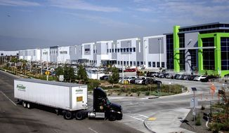 A semitruck turns into an Amazon Fulfillment center in Eastvale, Calif. on Thursday, Nov. 12, 2020, in this file photo. (Watchara Phomicinda/The Orange County Register via AP)  ** FILE **