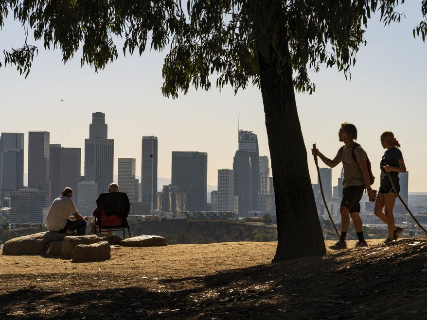 In this Monday, Jan. 11, 2021, file photo, people overlook the skyline of Los Angeles. California's population has declined for the first time in its history. State officials announced Friday, May 7 that the nation's most populous state lost 182,083 people in 2020. California's population is now just under 39.5 million. (AP Photo/Damian Dovarganes, File)