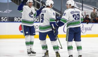 Vancouver Canucks' Travis Hamonic (27), J.T. Miller (9) and Nils Hoglander (36) celebrate a goal against the Edmonton Oilers during the first period of an NHL hockey game Thursday, May, 6, 2021, in Edmonton, Alberta. (Jason Franson/The Canadian Press via AP)