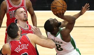 Boston Celtics guard Kemba Walker, right, shoots as Chicago Bulls center Nikola Vucevic and center Daniel Theis watch the ball during the first half of an NBA basketball game in Chicago, Friday, May 7, 2021. (AP Photo/Nam Y. Huh)