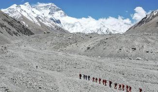 FILE - In this May 16, 2020, file photo released by Xinhua News Agency, Chinese surveyors hike toward a higher spot from the base camp on Mount Qomolangma at an altitude of 5,200 meters. China has opened the spring Everest claiming season from the northern approach amid strict measures to prevent the spread of COVID-19. A total of 38 people have been issued permits to climb the world's highest peak, known as Qomolongma in Tibetan, between March 31 and May 20, state media reported Friday, May 7, 2021. (Jigme Dorje/Xinhua via AP, File)