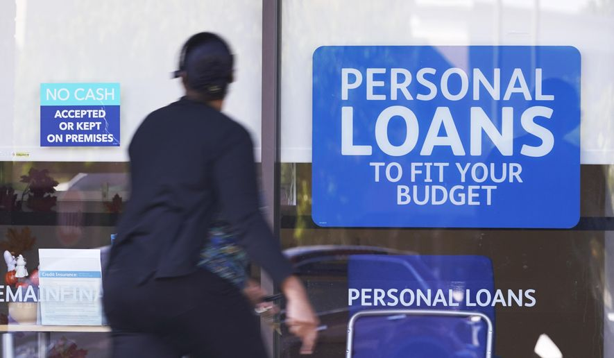 In this Oct. 1, 2020, photo, a woman walks past a personal finance loan office in Franklin, Tenn. U.S. consumer borrowing rose by a strong $25.8 billion in March 2021, the second-straight sizable monthly gain. The number released Friday, May 7 by the Federal Reserve represents another indication that the U.S. economic recovery is gaining steam.  (AP Photo/Mark Humphrey) **FILE**