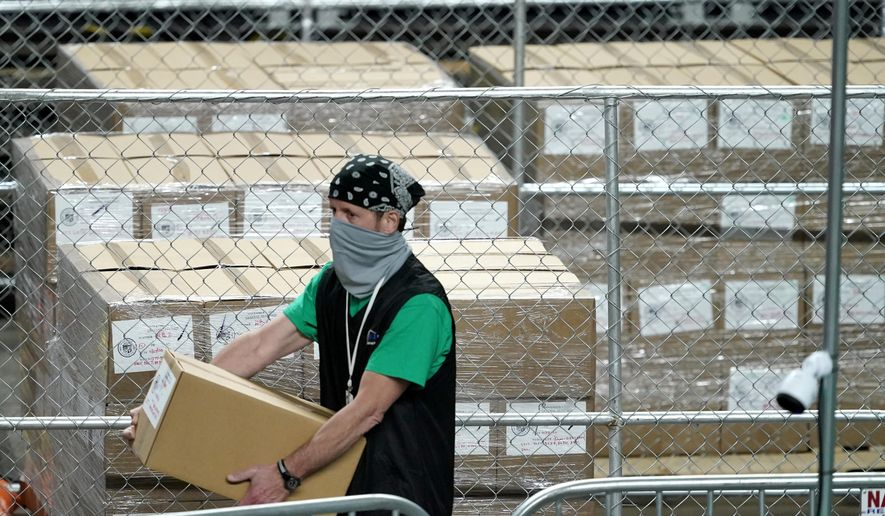 Maricopa County ballots cast in the 2020 general election are fenced in a secure area as a box is delivered to be examined and recounted by contractors working for Florida-based company, Cyber Ninjas, Thursday, May 6, 2021, at Veterans Memorial Coliseum in Phoenix. (AP Photo/Matt York, Pool) ** FILE **