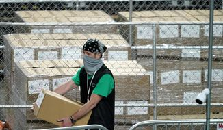 Maricopa County ballots cast in the 2020 general election are fenced in a secure area as a box is delivered to be examined and recounted by contractors working for Florida-based company, Cyber Ninjas, Thursday, May 6, 2021, at Veterans Memorial Coliseum in Phoenix. (AP Photo/Matt York, Pool)