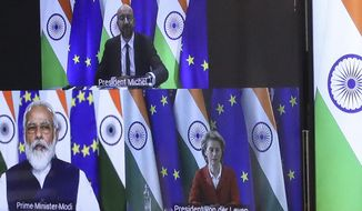 FILE- In this Wednesday, July 15, 2020 file photo, European Council President Charles Michel, top screen, and European Commission President Ursula von der Leyen, screen right, speak with India's Prime Minister Shri Narenda Modi during an EU-India videoconference summit from the EU Council building in Brussels. European Union leaders are meeting for a summit in Portugal on Friday, May 7 sending a signal they see the threat from COVID-19 on their continent as waning amid a quickening vaccine rollout. Their talks hope to repair some of the damage the coronavirus has caused in the bloc, in such areas as welfare and employment.  (Yves Herman, Pool Photo via AP, File)
