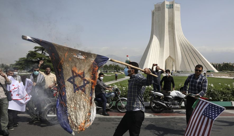 Demonstrators burn representations of Israeli and U.S flags during the annual Al-Quds, or Jerusalem, Day rally, with the Azadi (Freedom) monument tower seen at right, in Tehran, Iran, Friday, May 7, 2021. Iran held a limited anti-Israeli rally amid the coronavirus pandemic to mark the Quds Day. After the late Ayatollah Khomeini, leader of the Islamic Revolution and founder of present-day Iran, toppled the pro-Western Shah in 1979, he declared the last Friday of the Muslim holy month of Ramadan as an international day of struggle against Israel and for the liberation of Jerusalem. (AP Photo/Vahid Salemi)
