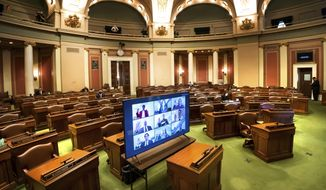 FILE - In this Jan. 5, 2021, file photo, legislatures are displayed on a monitor as they are sworn-remotely in groups of nine in the nearly-empty House Chamber at the Minnesota State Capitol, in St. Paul, Minn. As the Minnesota Legislature enters the last full week of its 2021 session, lawmakers face long hours of tough negotiations as they seek to agree on a balanced budget by the Monday, May 10, 2021, mandatory adjournment date. (Glen Stubbe/Star Tribune via AP, File)