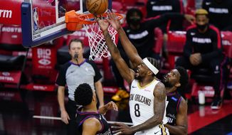 New Orleans Pelicans' Naji Marshall, center, goes up for a shot between Philadelphia 76ers' Joel Embiid, right, and Tobias Harris during the second half of an NBA basketball game, Friday, May 7, 2021, in Philadelphia. (AP Photo/Matt Slocum)
