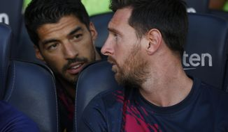 FILE - In this Sunday, Aug. 4, 2019 file photo, Barcelona's Lionel Messi, right, talks with teammate Luis Suarez on the bench before the Joan Gamper trophy soccer match against Arsenal at the Camp Nou stadium in Barcelona, Spain. Luis Suarez and Lionel Messi spent years hanging out at their neighboring homes on the Mediterranean coast when taking a break from scoring goals for Barcelona. On Saturday, May 8, 2021 Suarez will return to Camp Nou aiming to knock his former team out of the Spanish league title race.(AP Photo/Joan Monfort, file)