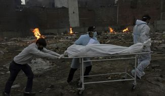 Body of a COVID-19 victim is wheeled in for cremation in a ground that has been converted into a crematorium in New Delhi, India, Thursday, May 6, 2021. Infections in India hit another grim daily record on Thursday as demand for medical oxygen jumped seven-fold and the government denied reports that it was slow in distributing life-saving supplies from abroad. (AP Photo/Ishant Chauhan)