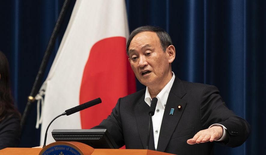 Japanese Prime Minister Yoshihide Suga responds to a reporter's question after he spoke at a news conference in Tokyo on Friday, May 7, 2021. Suga announced an extension of a state of emergency in Tokyo and other areas through May 31. (AP Photo/Hiro Komae)