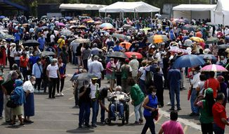 FILE - In this April 12, 2021 file photo, people over age 60 line up to be vaccinated with the AstraZeneca COVID-19 vaccine at the University Olympic Stadium in Mexico City. Mexico City's government announced on Friday, May 7, 2021 that public hospitals dedicated to fighting COVID-19 are experiencing their lowest rate occupancy of the pandemic and the city is slightly easing some restrictions, more than three months after infections peaked in the Mexican capital in January. (AP Photo/Marco Ugarte, File)