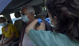 Manuel Santamaria, 76, receives a shot of Pfizer vaccine during a COVID-19 vaccination campaign, in Pamplona, northern Spain, Friday, May 7, 2021.(AP Photo/Alvaro Barrientos)
