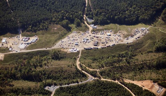 FILE - In this Sept. 20, 2016 file photo vehicles are seen near Colonial Pipeline in Helena, Ala.  A major pipeline that transports fuels along the East Coast says it had to stop operations because it was the victim of a cyberattack. Colonial Pipeline said in a statement late Friday that it took certain systems offline to contain the threat, which has temporarily halted all pipeline operations, and affected some of our IT systems. (AP Photo/Brynn Anderson, File)