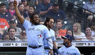 Toronto Blue Jays' Vladimir Guerrero Jr., left, celebrates Cavan Biggio's two-run home run during the second inning of the team's baseball game against the Houston Astros, Saturday, May 8, 2021, in Houston. (AP Photo/Eric Christian Smith)