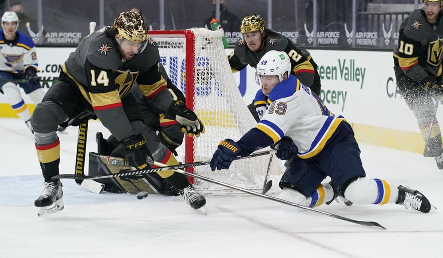 St. Louis Blues center Ivan Barbashev (49) attempts a wrap around shot against Vegas Golden Knights defenseman Nicolas Hague (14) during the third period of an NHL hockey game Friday, May 7, 2021, in Las Vegas. (AP Photo/John Locher)