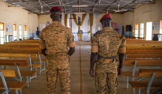 Two soldiers stand in the Catholic church at the 10th RCAS army barracks in Kaya, Burkina Faso, Saturday, April 10, 2021. Once considered a beacon of peace and religious coexistence in the region, the West African nation has been embroiled in unprecedented violence linked to al-Qaida and the Islamic State since 2016, throwing an ill-equipped and undertrained army into disarray — and overwhelming the chaplains tasked with supporting them. (AP Photo/Sophie Garcia)