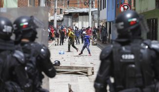 Anti-government protesters clash with police in Gachancipa, Colombia, Friday, May 7, 2021. The protests that began last week over a tax reform proposal continue despite President Ivan Duque's withdrawal of the tax plan on Sunday, May 2. (AP Photo/Ivan Valencia)