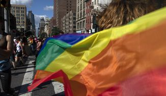 In this June 30, 2019, photo, parade-goers carrying rainbow flags walk down a street during the LBGTQ Pride march in New York, to celebrate five decades of LGBTQ pride, marking the 50th anniversary of the police raid that sparked the modern-day gay rights movement. (AP Photo/Wong Maye-E) **FILE**